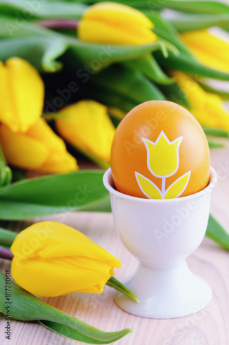 Easter egg in a cup with bunch of fresh yellow tulips