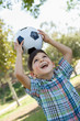 Cute Young Boy Playing with Soccer Ball Outdoors in the Park.