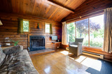 Cozy interior of a rustic log cabin with a view of a garden. - 187786830