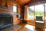 Cozy interior of a rustic log cabin with a view of a garden. - 187786848