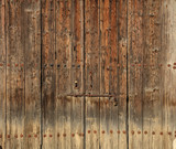 Wooden brown timeworn door. Space for text backdrop, rusty latch and padlock. Closeup view, details.