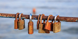 Rusty padlocks has been locked on a peeled railing. Blurred background, close up view with details.