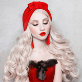 Luxurious blonde woman with beautiful long white hair and red lips in a red turban on a gray background.