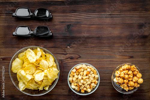 Cinema food. Crisp, popcorn, rusks near glasses on dark wooden background top view copy space