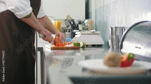 Poster Chief on the kitchen of restaurant cuts vegetables for salad - cooking concept