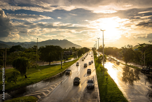 Rainy Wet Highway With Vehicles Driving by Sunset - 187795800