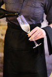Sommelier pours sparkling wine into the wineglass of the guest in the restaurant - 187803699