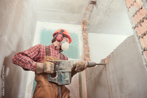 worker with demolition hammer breaking interior wall - 187804663