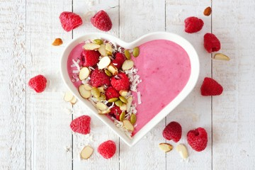 Healthy raspberry smoothie in a heart shaped bowl with superfoods. Above scene on a white wood background.