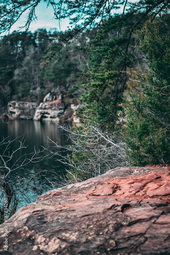 Cliff By Crystal Clear Lake Surrounded by Green Trees - 187834260