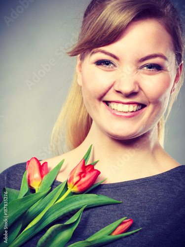 Happy blonde woman with spring flower.