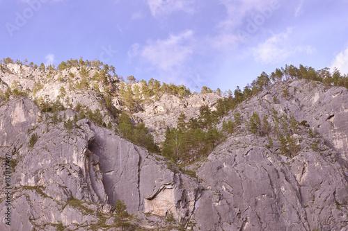 Papiers peints Lavende High gray rocks. Green trees. Blue sky