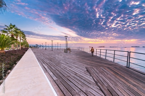Foto op Plexiglas Cyprus Molos Promenade and skyline of the coast in Limassol city in Cyprus at cloudy sunrise. View of boardwalk pier path landmark with palm trees, pools of water, the Mediterranean sea and people walking.