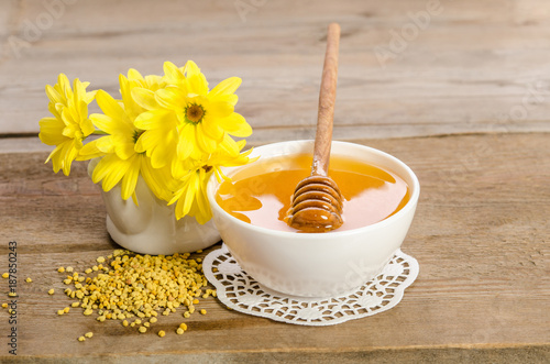 Fotobehang Bee Yellow flowers and bee products (honey, pollen) on wooden background