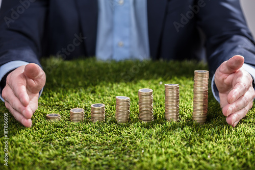 Foto Murales Businessman Protecting Stacked Coins On Grass