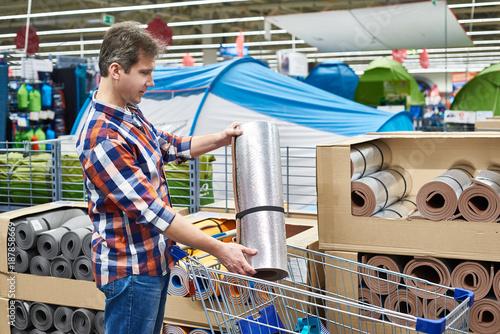 Foto Murales man chooses a tourist rug in sports shop