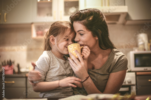 Mother and daughter have fun together. Mommy let me try coffee.