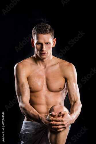 Poster muscular young sportsman holding knee in hands and looking at camera isolated on black