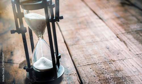 Closeup of an hourglass in wooden background