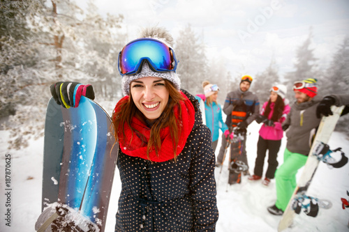 Sporty female holds snowboard in mountains on winter