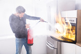 Man Using Fire Extinguisher To Stop Fire Coming From Oven - 187870844