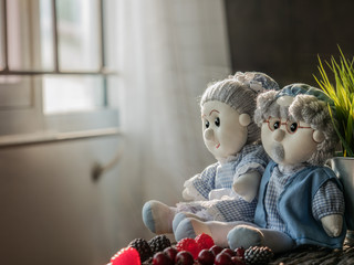 Still life visual arts of grandparent lovers dolls made of cloth setting to sit beside one other near the window with warm sunlight ray on a wooden slab