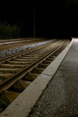 Ruhiger einsamer verlassener Bahnsteig bei Nacht mit Laternenlicht