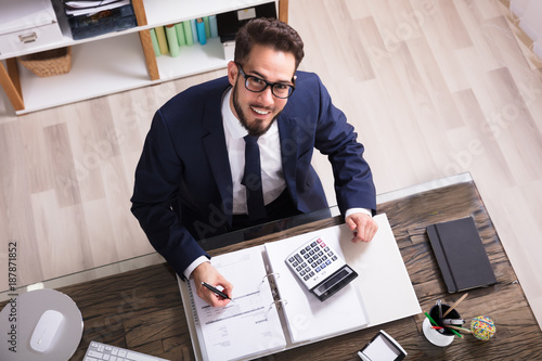Happy Businessman Calculating Bill In Office