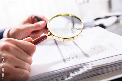Foto op Aluminium Kasteel Businessperson Checking Bill With Magnifying Glass