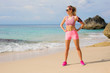 Fit athletic woman standing on the beach ready for workout