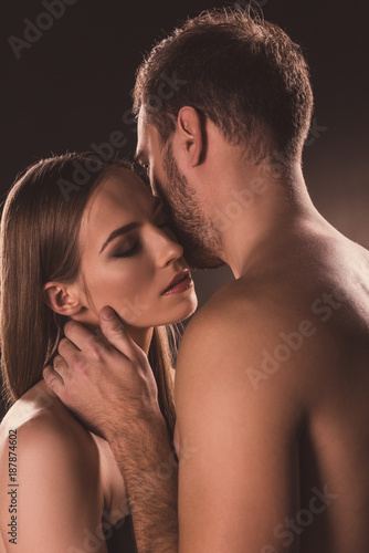 sensual nude lovers hugging with closed eyes, on brown