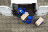 Two Delivery Men Unloading Cardboard Box From Truck - 187877888