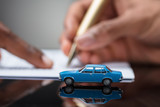 Person's Hand Signing Car Loan Agreement Contract