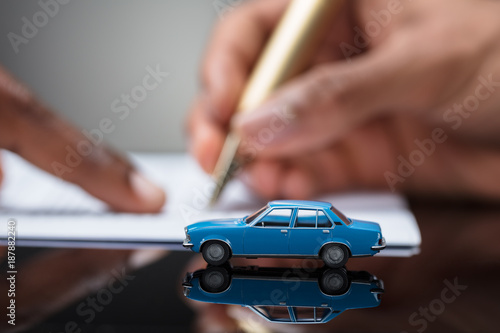 Fototapeta Person's Hand Signing Car Loan Agreement Contract