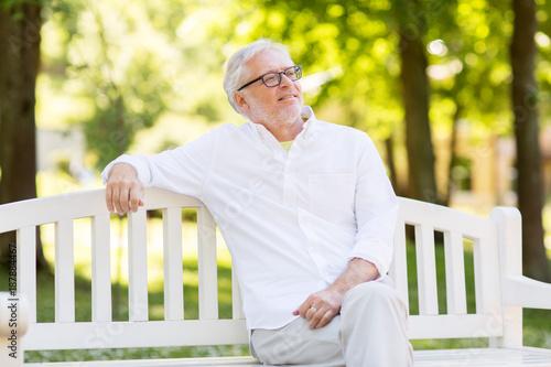 Foto Murales happy senior man in glasses sitting at summer park