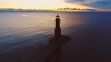 Iconic red Lighthouse silhouetted against dramatic Lake Michigan, dawn. Moving aerial view.  - 187886890