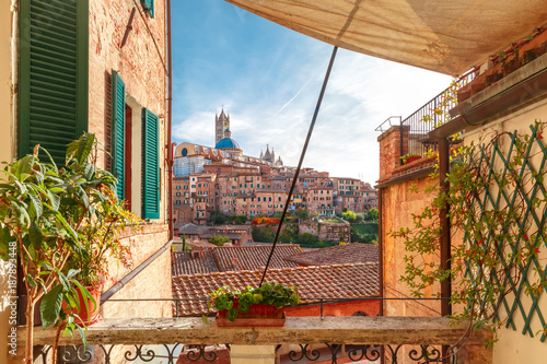 Poster Toscane Beautiful view of Dome and campanile of Siena Cathedral, Duomo di Siena, and Old Town of medieval city of Siena in the sunny day through autumn leaves, Tuscany, Italy