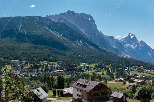 Foto Murales Green Meadow and Typical Houses among Mountains Scenery in Summer Time