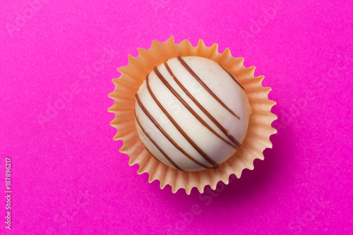 Homemade white chocolate truffle. Flat design of candy ball over pink color. - 187896217