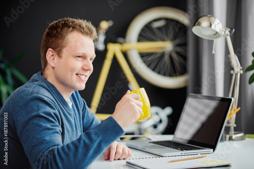 Businessman drinking coffee and sitting in modern home office