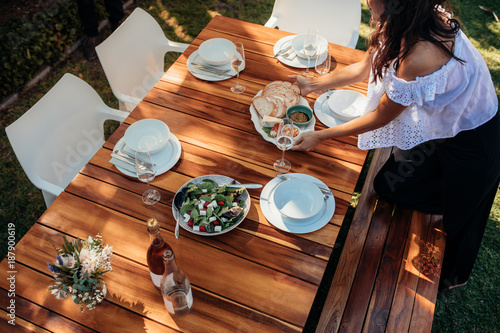 Foto Murales Woman setting food on table for housewarming