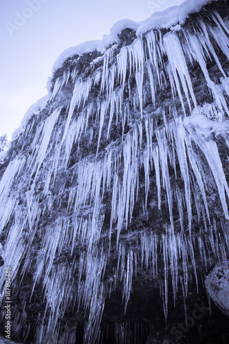 close up of huge icicles on mountain rock wall beside waterfall pericnik - 187907488