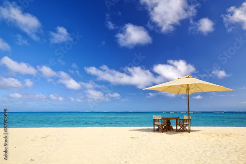 Foto Murales Table, chairs and umbrella on sand beach in Mauritius Island