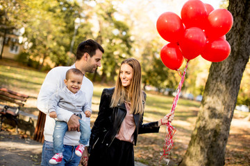 Happy young parents with baby boy in autumn park holding red balloons