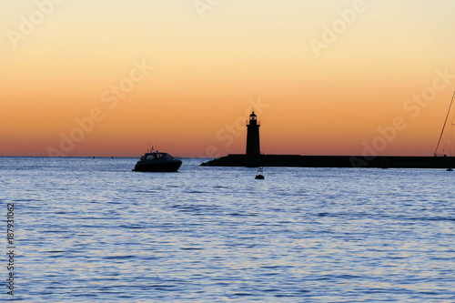 Silhouette of the lighthouse in the sea at sunset. Poster