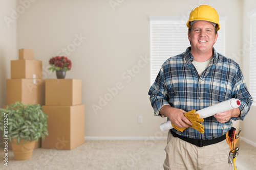 Contractor With Plans and Hard Hat Inside Empty Room with Moving Boxes.