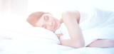 Beautiful girl sleeps in the bedroom, lying on bed - 187937416