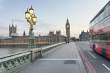 Red bus speeding up along Westminster Bridge at sunset, London - UK