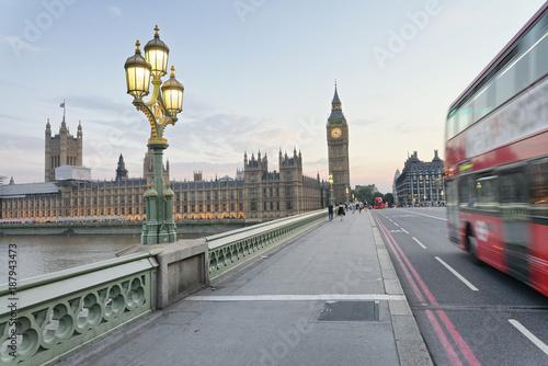 Red bus speeding up along Westminster Bridge at sunset, London - UK - 187943473
