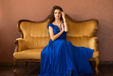 A beautiful model in a blue dress is sitting on a yellow sofa - 187950480